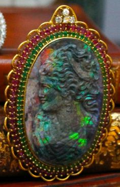Rare Large Carved Black Opal Cameo Pendant/Brooch set in 18k Yellow Gold, surrounded by Rubies, Emeralds, and Diamonds.