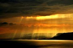 De gros et menaçants nuages noirs... La mer... et au loin les ombres de montagnes en plateaux.. Un léger voile de rayons de soleil, tendres et doux, effleurent cette toile en profondeur, inondant la mer et le ciel d'une lumière dorée cotoneuse! C'est splendide, tout simplement! Merci la Vie!