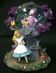 """Alice & Chesire Cat Snowglobe Alice in Wonderland Description: Alice tries to decide which path to take. Characters: Alice, Cheshire Cat, Features: Cheshire Cat's face lights up. Music: """"I'm Late"""" Size: 8"""" H Snow: Source: Timeframe: ORP:"""
