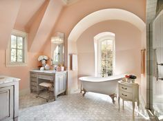 The daughter's bathroom is distinctly feminine in feel with soft blush walls in Farrow & Ball's Calamine paint. A two-drawer commode from Restoration Hardware and an antique stool offer another layer of elegance. Carrara marble flooring, purchased through Granite & Marble Resources, adds visual interest.