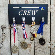 Award Board for hanging medals won at regattas. Each hook holds several medals.