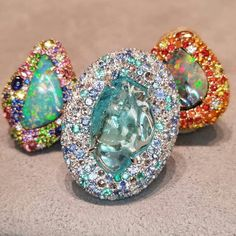 """#Paraibalicious & #Opalicious!!! @margotmckinney IS AT THE BRAND NEW @neimanmarcus in #FortWorth!!! A tumbled #ParaibaTourmaline """"Pebble"""" surrounded by #RoseCut Diamonds, #Sapphires, #Tanzanite, and even MORE #Paraiba #Tourmaline! Juicy #BlackOpal rings in the background."""
