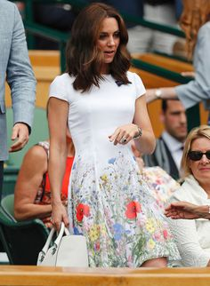 For her second appearance at Wimbledon, Kate Middleton kept things light in a white knee-length dress featuring a vibrant floral pattern around the hem. She carried a white tote by Victoria Beckham and accessorized her look with a silver watch. She opted for a neutral makeup look with a subtle lip.