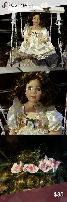 Very very beautiful porcelain doll Very excellent condition. She has beautiful flowers on her dress and headpiece and beautiful flowers on the sides of the swing and top of the swing. Her dress has pearls and Lace. And she can be removed off the swing Other