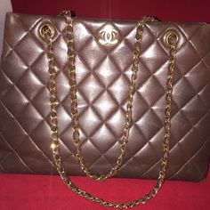 """Chanel Chocolate Brown Tote 4x HP Host Pick """"Total Trendsetter"""" """"Fall Favorites"""" """"Downtown Chic"""" """"2016 Trends"""" Authentic Chanel chocolate brown tote with gold hardware. Purse has snap closure, inside zipper pocket & inside open pocket. Measurements 12.5"""" long x 9.5"""" tall x 4"""" wide. Purse does show normal signs of wear. Some light scuffs on the surface & corners show wear. Can be taken to Chanel to condition the leather. I took pictures with a flash so the scuffs are visible. I no longer have…"""