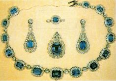 Sapphire Necklace: The George VI and Modern Sapphire Set. The set features a necklace of emerald-cut sapphires surrounded by diamonds and separated by individual diamonds, plus a pair of pendant earrings, each with a single large sapphire in a diamond cluster. These pieces are set in gold.