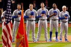 Manager Joe Maddon #70, Dexter Fowler #24, Kris Bryant #17, Anthony Rizzo #44 and Ben Zobrist #18 of the Chicago Cubs stands during the national anthem prior to Game One of the 2016 World Series against the Cleveland Indians at Progressive Field on October 25, 2016 in Cleveland, Ohio.