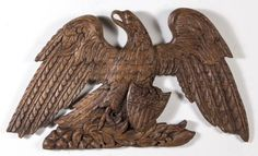 FOLK ART CARVED WALNUT EAGLE PLAQUE,  spread-winged form clutching a patriotic shield, naturalistic base, old surface with warm color.