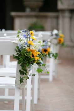 Sunflower aisle decorations on the white folding chairs with purple and white baby's breath in white vintage holder vase | villasiena.cc