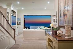 The best view in the house, this comfortable sectional looks out on a stunning Pacific Ocean seascape. Traditional-style built-ins house a TV and other media components, while sisal rugs add a softness to the hardwood floors.