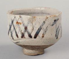 """志野遠山檜垣文茶碗 銘「山路」  美濃焼   時代桃山時代 16世紀    志野は、桃山時代の天正・文禄年間(1573~96)頃に美濃で作られた、わが国最初の白い釉のかかった焼きものである。温かく柔らかい感じのする、わが国独特の焼きものとして、多くの人から親しみをもたれている。この茶碗は、百草土と呼ばれる志野特有の柔らかみのある土を用いて、厚手で大振りに挽き上げられている。志野茶碗としては""""作意""""(創意工夫)のある姿で、腰は高く、見込みが深い。口縁は山の端風に変化をつけ、これに呼応した気分で腰回りに箆目を一条引いている。胴には遠山に檜垣と松を鉄絵具で描き、その上に長石釉を厚くかけている。釉は滑らかに溶けて釉肌に温かみを感じさせ、火色も見えている。内箱蓋表に金粉字形で「志野 山路」と記されている。   時代桃山時代 16世紀 サイズ高10.3 口径13.6×12.0"""