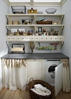 Skirts hide the washer/dryer. I also LOVE the shelving and the row of tiny drawers! What in the world would you keep in them all? That row of drawers would be superb in a sewing room!