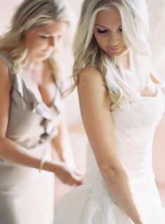 LOVE this shot of the mother of the bride helping her daughter with her dress.