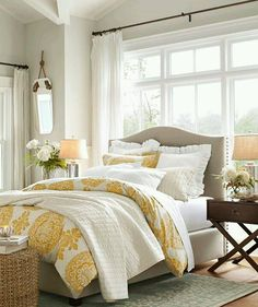 Taupe and yellow bedroom with bright windows.