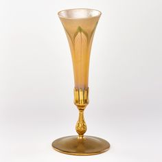 46: TIFFANY STUDIOS Estimate: $1,000 - $1,500  Gold Favrile glass pulled-feather vase with gilt bronze base, New York, 1911; Base stamped TIFFANY STUDIOS NEW YORK S1911