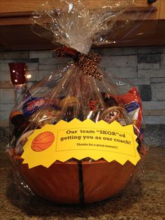 Gift basket for our basketball coach. I used a basketball bowl from Party City & included: peanuts, Gatorade, root beer bottles, cracker jacks , jerkey, skor bars, and a gift card for a pizza place.