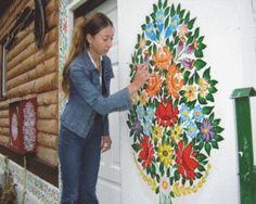 Artesã dá retoques na pintura de parede, com motivos florais no estilo de Zalipie, a 'vila pintada' da Polônia.