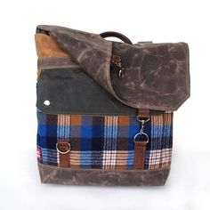 This water resistant backpack is made with waxed cotton canvas in shades of brown. ginger and walnut, oiled leather, and features pockets of virgin plaid wool from the 1960s in gingerbread, navy white and bright blue. This one is completely unique -- you will be receiving the exact bag