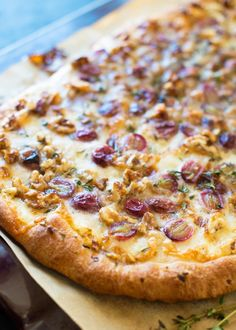 Grape and Taleggio Flatbread Recipe. This is a unique and EASY way to put store bought pizza dough to use. Great appetizer or finger food for a girls' night in, or a grown-up weeknight dinner that comes together in a flash!  You'll need pizza dough, olive oil, garlic, thyme, taleggio, grapes, and walnuts.