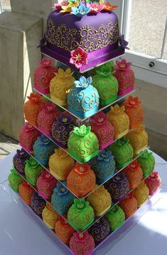 This cake was made by the Rachel Hill of Planet Cake. Beautiful colors and intricate designs cover the mini wedding cakes in six tiers. This unusual wedding cake was made for a couple for their Indian Bollywood wedding.