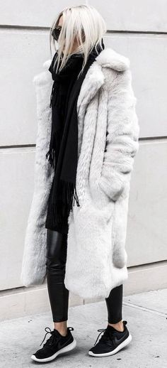 cozy winter outfit idea : fur coat sweater skinnies sneakers scarf