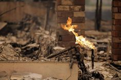 A flame burns from an open gas line in a partially-destroyed neighborhood in Middletown, Calif., on Sunday, September 13, 2015, the day after a wildfire swept through town destroying homes and forcing mass evuations. PG&E crews were making their way through the area shutting off electrical and gas services and removing downed power lines. Photo: Carlos Avila Gonzalez, The Chronicle