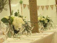 vases of whites and greens including hydrangea, roses, lisianthus and stocks