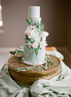 white, mint green, and gold multi-layer wedding cake with flower...