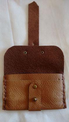 Porta cartão feito em couro cor creme legítimo <br>Costuras laterais feitas à mão, cordão super resistente. <br>Botão carrapeta regulagem de 2 furos <br>Medida: 10 cm x 6,5 cm <br>Cabem aproximadamente 10 cartões.