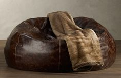 Grand Leather Bean Bag Chair  Like an old baseball mitt, this plump, over-sized bean bag chair is upholstered in fine leather and seamed with a circular center for sink-in comfort. It features a velvet bottom, topstitching detail, a child-safe locking zipper on bottom of bag and comes in Brompton Cocoa, Glove, Saddle, Cognac, Chestnut or Slate.