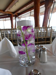 Orchid stem in a cylinder vase with a floating candle at Bali Hai in San Diego