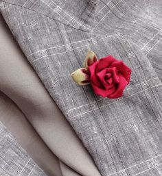 An red rose silk lapel pin flower, made in the Japanese tsumami kanzashi style! I used an raspberry silk jacquard and green iridescent silk to create this rose with leaves lapel pin, and mounted it onto a tie tack finding. Complements a suit, blazer, hat, cardigan or sports jacket, or formal wear for a wedding. Kanzashi flowers are made from folded fabric squares, one petal at a time. Originally, apprentice geisha made kanzashi hair accessories from their old kimonos. DETAILS  ---silk…