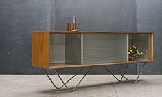 USA, c.1950s. Designer Unknown. Vintage Mid-Century Modern Cabinet, possibly a Prototype Design resembling work from Florence Knoll and Vladimir Kagan, as well as Raymond Loewy and George Nelson.  High Quality Parts and Construction, Grey Painted Interior, Elongated Chromed Brass or Copper Hairpins Supports, Molded and Smooth Glass Sliding Doors. Three Sectioned Openings. Fair Vintage Condition sh
