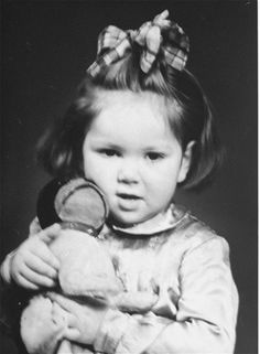 Henia Wisgardisky in Kovno ghetto holding a doll.  Henia was hidden in a secret room her father built before she was smuggled out of Kovno.