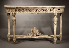 An Italian Neoclassic white-painted console table, Late 18th / early 19th century, probably Naples or Rome, the D-shaped variegated white marble top above a pierced foliate-guilloche-carved frieze centered by an acanthus spray, over acanthus-headed turned tapering fluted legs joined by an incurved stretcher centered by an urn issuing floral garlands, on foliate-carved tapering feet.
