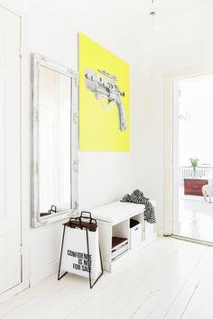Eteisen matala penkkihylly on kuulunut sisustukseen myös Emmin ja Hannun aiemmissa kodeissa. Lehtiteline on hankittu Kaapelitehtaan designmyyjäisistä, suuri peili on kirpputorilta. Peili oli ostohetkellä kullanvärinen, mutta Emmi spraymaalasi sen valkoiseksi. Peilin vieressä oleva voimakkaan keltainen teos on Leena Niivuoren.