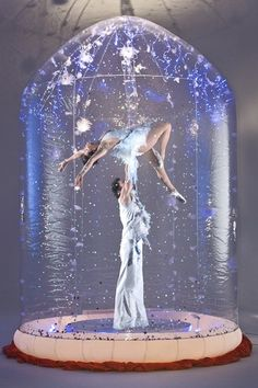Winter wedding entertainment ideas: A unique and visually beautiful addition to any event, the Magical Snowdome will captivate any audience. Combining graceful acrobatics and amazing balancing displays, with glitter continuously falling over them, the Magical Snowdome is a striking act that your guests will not forget.  #Winter #WinterWedding #WinterWeddings #WinterWeddingIdeas #WeddingIdeas #WinterWeddingEntertainment