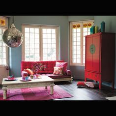 Special attention to the lovely crimson wooden cabinet with a lock inspired from the traditional Chinese cabinets.