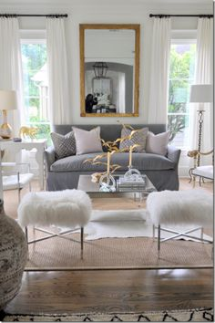 grey living room.... love the fluffy matching stools, large mirror, small velvet sofa and big windows :)