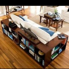 Love the idea of outlining the couch with short bookshelves, especially on slippery hardwood floors! But not sure if our living room would be big enough...