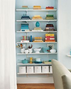 Shelving saves the day! Floor-to ceiling shelves can help to organize all that stuff you've collected over the years. Another lesson: Storage can be beautiful. The books are stacked horizontally by color.