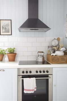 Gorgeous Kitchen!  Love the white brick with stainless steel appliances and hint of green w/ terra-cotta pots...