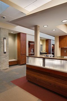 Healthcare Community Hospital in McCook, Nebraska.  The carpeted reception area in the front lobby welcomes visitors with rustic stone, soft light, and warm wood accents.