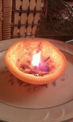 """DIY candle from an orange. Juct cut off the top, scoop out orange sections, straighten natural """"wick"""", add olive oil, and light. Voila! I added cinammon and cloves to the oil as well. Smells wonderful!"""