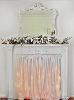 If too hot for fire at Christmas time (likely), could do this; find my short white curtains and use the tension rods and lights I already have....(use one rod inside to hang lights, one at front for curtain); festive but not hot.