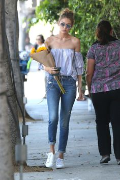 Gigi Hadid wears a boyish striped off-the-shoulder Misa Los Angeles top with casual and cuffed faded jeans, white-trimmed shades, coordinating sneakers—and a bouquet of sunflowers.