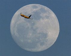 A United Airlines jet taking off from Newark Liberty International Airport flies across the moon seen from Eagle Rock Reservation in West Orange, N.J., Thursday, April 5, 2012. (AP Photo/Julio Cortez)