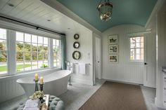 "The window behind the tub features remote-controlled blinds, and the lovely blue curtains match the curtains in the master bedroom. ""It is a very luxurious, spa-like experience in the bathroom,"" says the home's interior designer Linda Woodrum. ""And we have beautiful drapery, so it is a very elegant and very tailored room."""