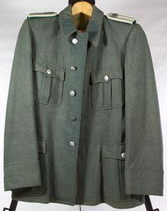 Lot 537: World War II German Nazi Paymaster Tunic; Light green wool coat with partial cotton twill lining and metal belt hooks on the side seams