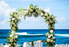 A beautiful arch made of greenery and white flowers for an oceanfront wedding ceremony at The Beach House